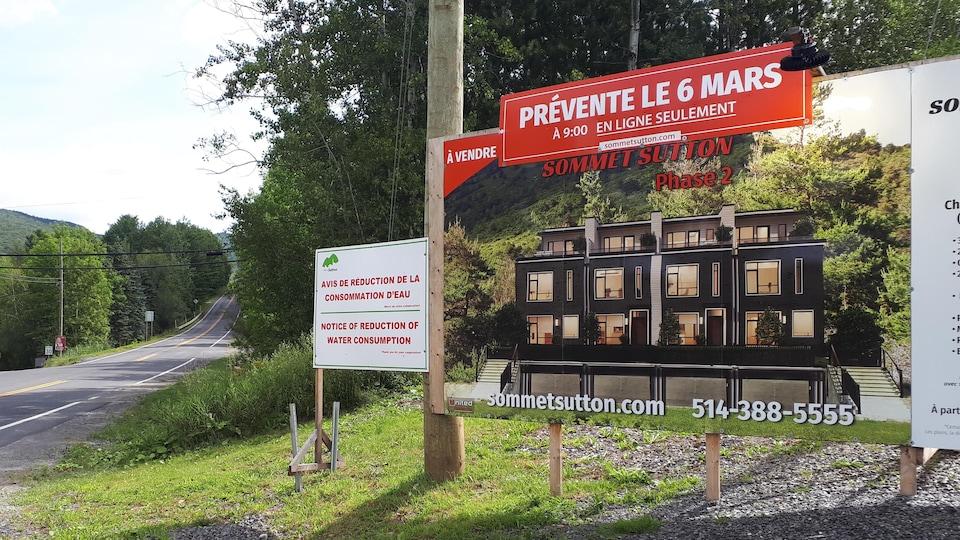 Une affiche en bord de route demande de réduire la consommation d'eau. À côté, une affiche fait la promotion d'un nouveau développement immobilier.