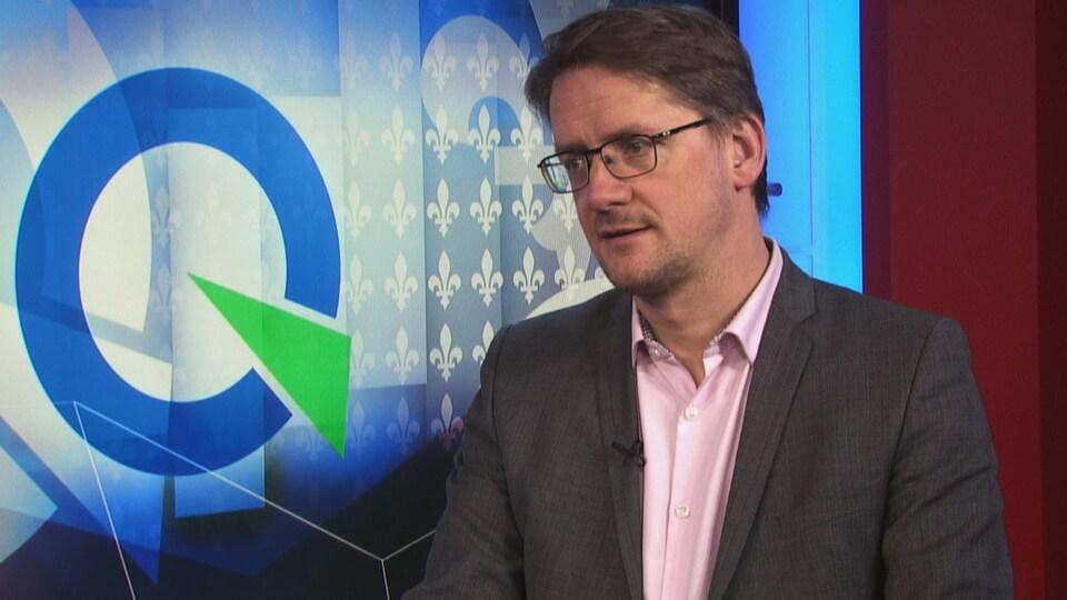 Sylvain Gaudreault devant un téléviseur qui affiche le logo du Parti québécois.