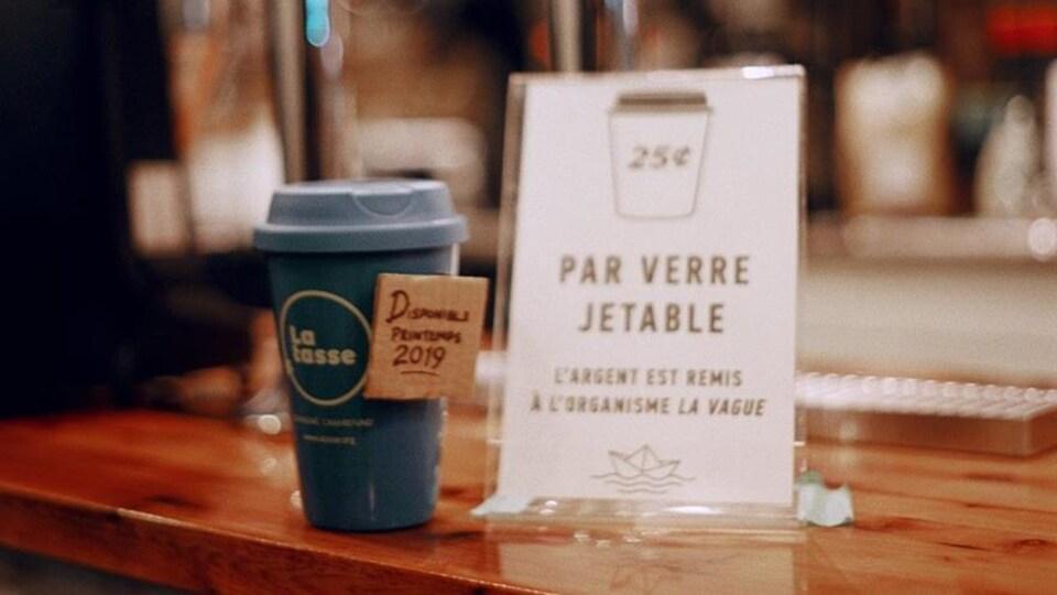Image d'une tasse et d'une affiche indiquant que des frais de 25 cents par tasse jetable sont ajoutés à la facture. L'argent est remis à l'organisme La vague.