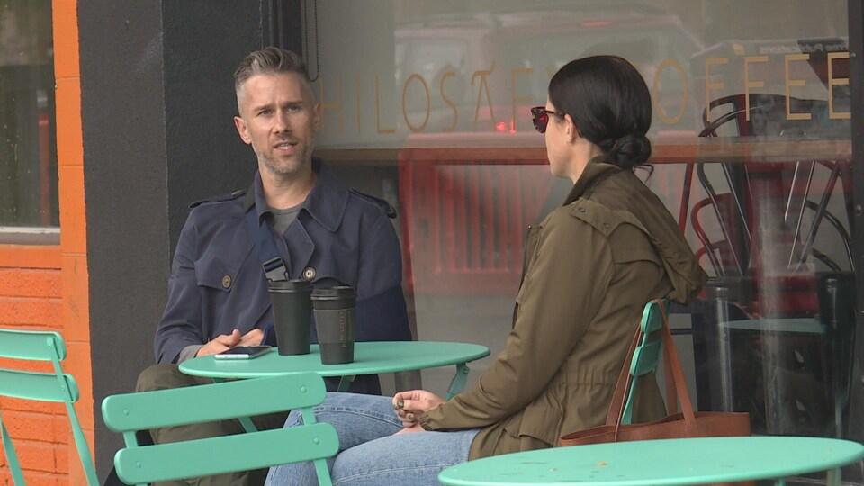 Douglas Crossman et Ashley Popko boivent un café attablés à l'extérieur.