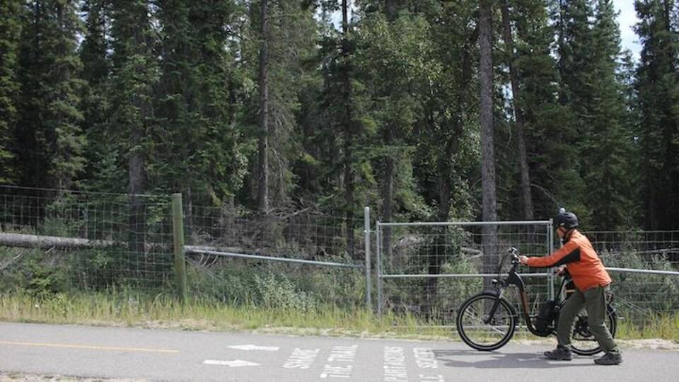 Un cycliste pousse son vélo électrique sur une route.