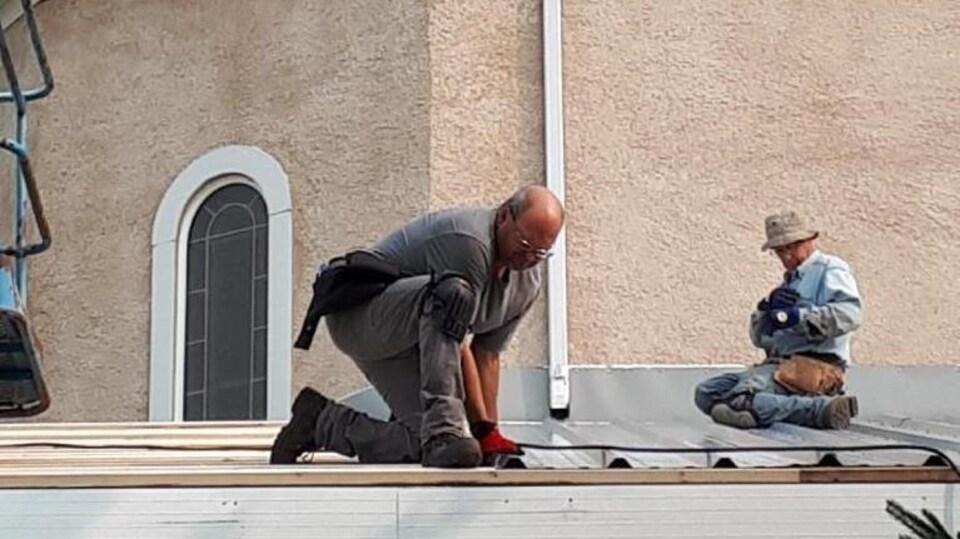 Une photo des rénovations de l'église. Michel Moyen et Armand Marchildon mettent la tôle sur le toit