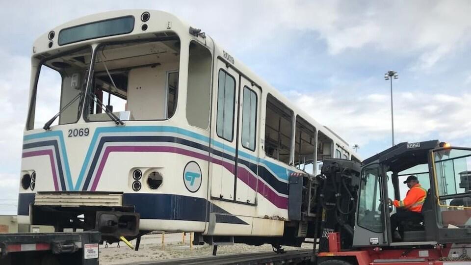 Un wagon de train qui se trouve sur la plateforme d'un camion est soulevé par un chariot élévateur. Un homme qui porte une veste de sécurité est agenouillé devant le camion et regarde le travail du cariste.
