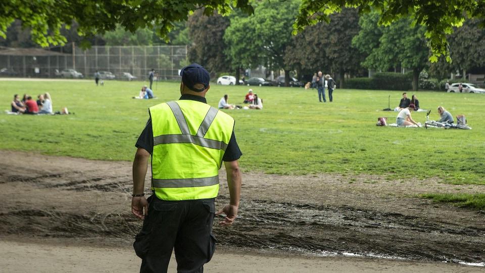 Un agent municipal vêtu d'un gilet jaune regarde des personnes assises dans un parc.