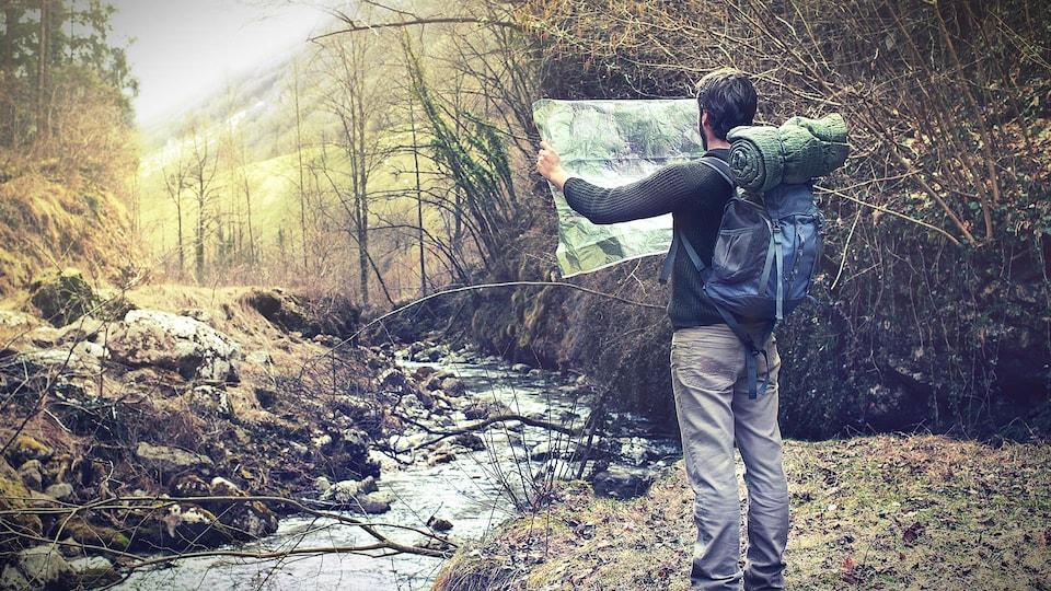 Un homme debout dans une forêt avec un sac à dos qui tient et regarde une carte.