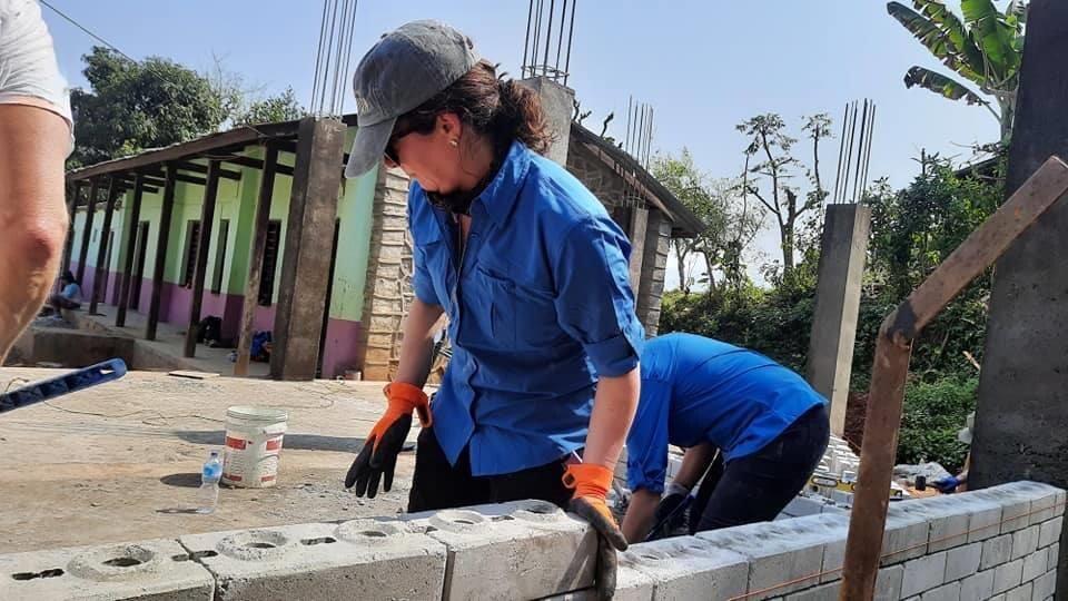Valerie Denis pose des blocs de béton pour construire un mur.