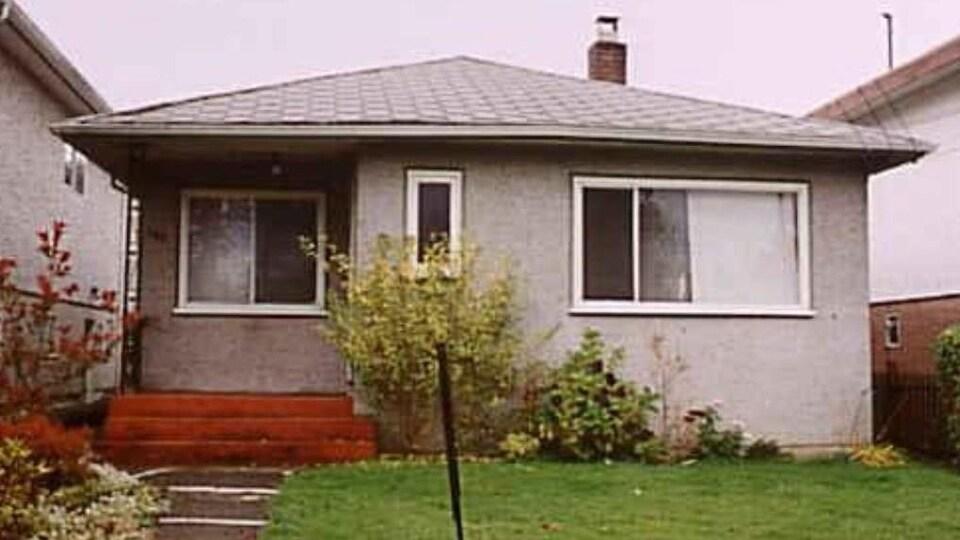 Façade d'une maison de style bungalow qui a l'air assez petite et vieille.