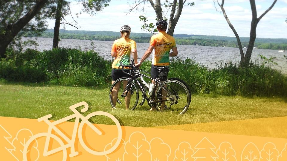Un couple debout à côté de leurs bicyclettes en train de regarder un lac et ses environs.