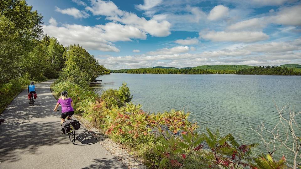 Des cyclistes sur une piste le long d'un lac.