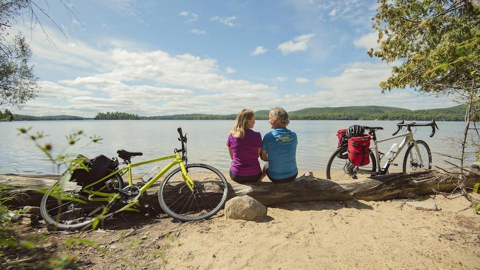 Un couple assis sur une plage devant un lac entouré de leurs bicyclettes.