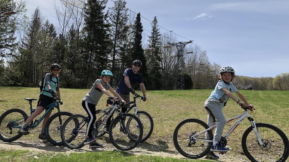 Une famille pose devant la caméra, chacun sur son vélo.