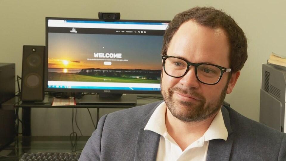 Un homme portant des lunettes et un écran d'un ordinateur au fond avec l'inscription « Welcome ».