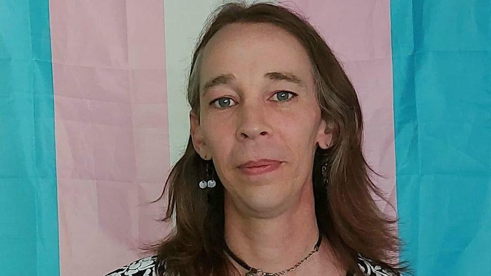 Une femme qui sourit devant le drapeau de la fierté transgenre.