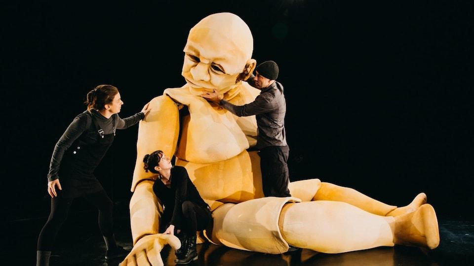 Trois personnes sur une scène de théâtre avec une marionnette géante.