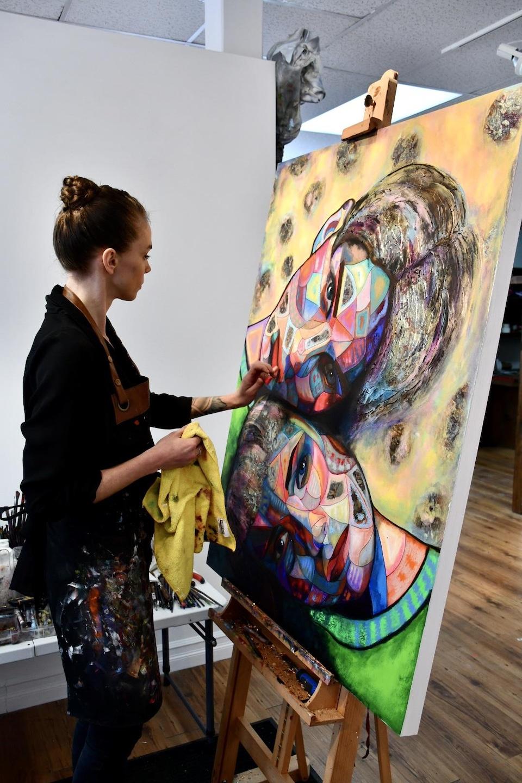 Une femme peint une toile où deux amoureux se collent tendrement.