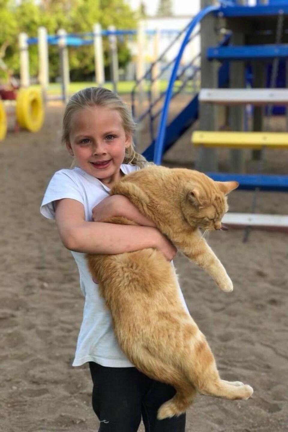Un chat dans les bras d'un enfant dans un parc