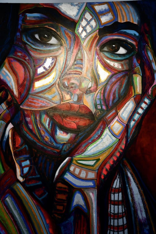 Une toile représente un visage de femme.