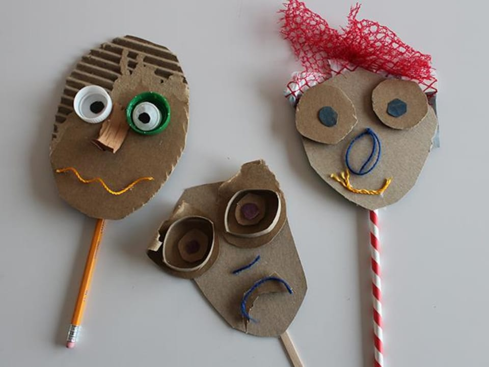 Trois marionnettes en carton fabriquées avec divers objets.