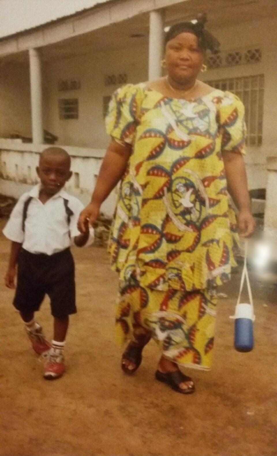 Un enfant tient la main de sa mère