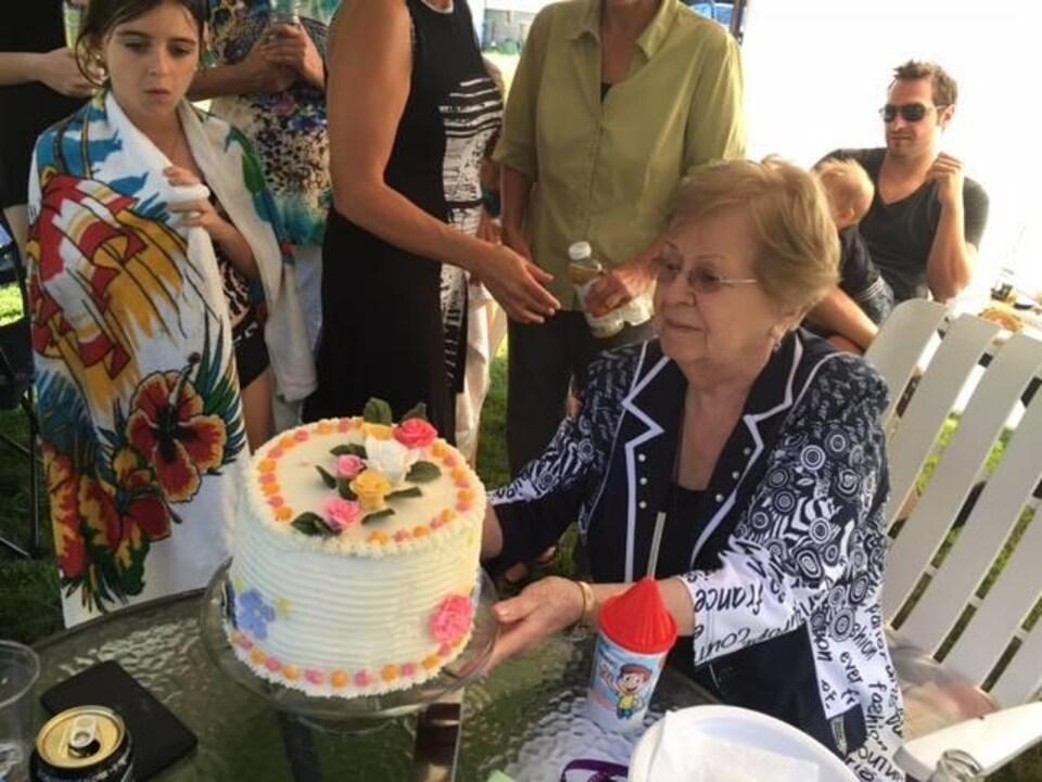 Une dame avec son gâteau pour son 90e anniversaire. Le gâteau est décoré avec des fleurs en sucre.