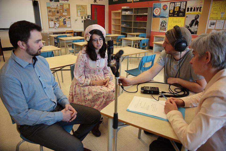 Captation d'une entrevue dans une salle de classe. Un homme et une femme sont en entrevue au micro. Un homme portant une tuque et un casque d'écoute enregistre leurs propos. L'intervieweuse écoute attentivement.