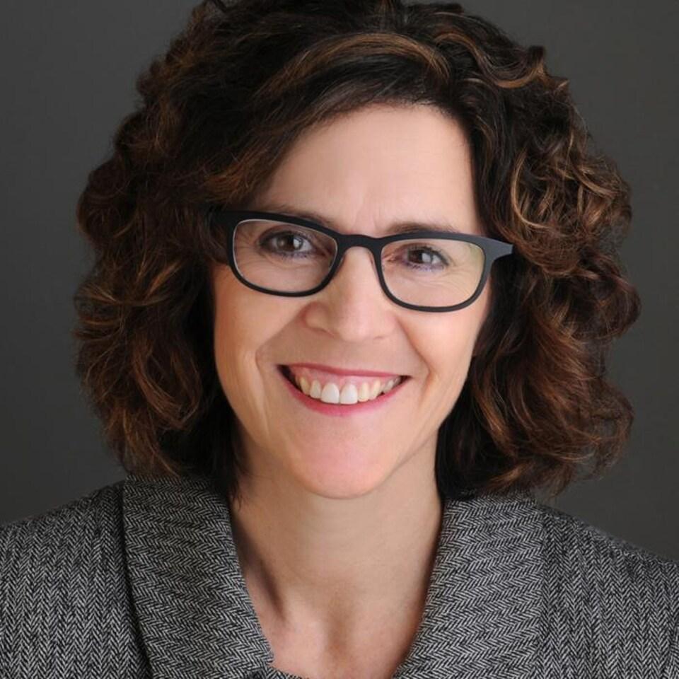 Une femme portant des lunettes sourit.