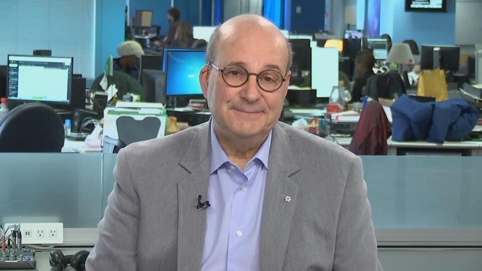 Un homme avec des lunettes rondes sourit devant une salle de nouvelles.