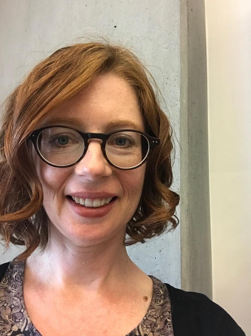 Une femme portant des lunettes sourit
