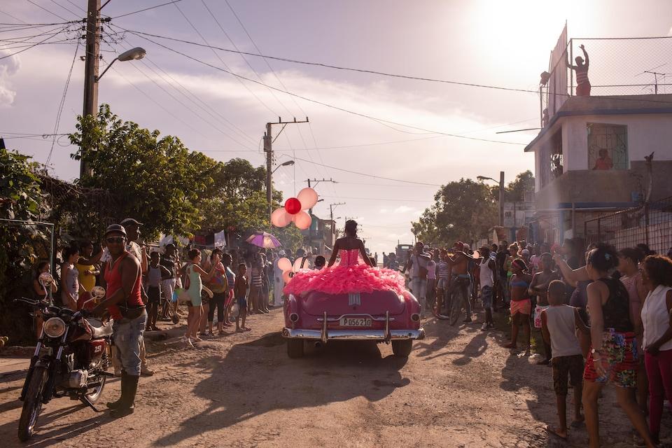 La voiture est au milieu de la rue et il y a des dizaines de personnes de chaque côté.