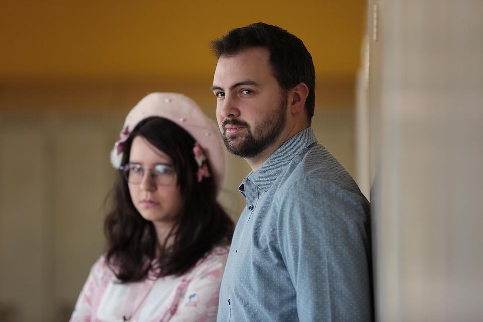 Une femme et un homme dans la vingtaine sont appuyés sur des casiers. Ils regardent au loin.