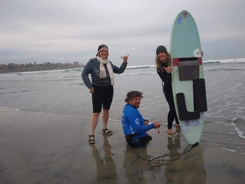 Le surfeur Scott Patterson s'apprête à entrer à l'eau avec l'aide de Pascale Martineau qui tient sa planche.