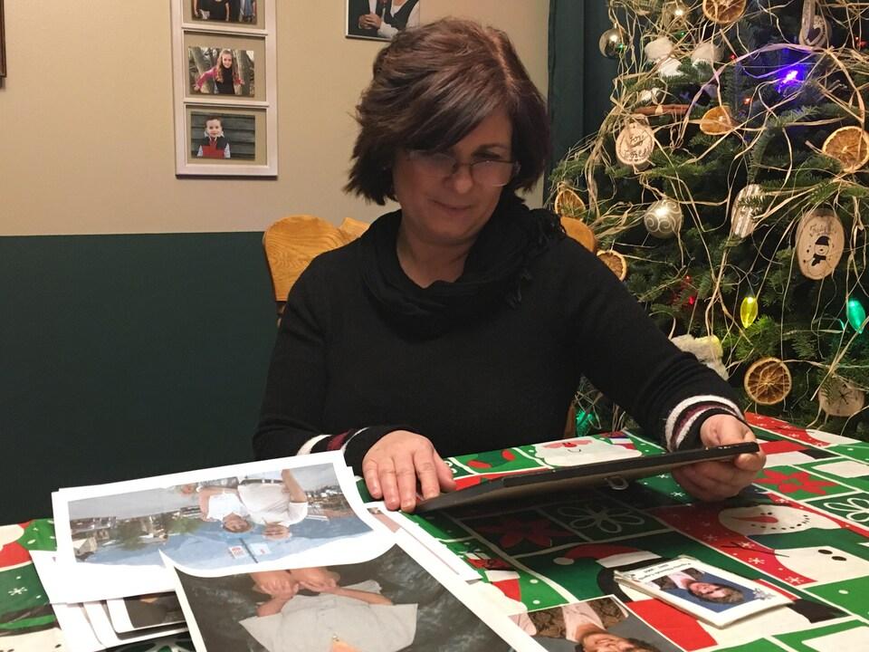 Une femme brune tient un cadre dans ses mains devant un sapin de Noël.