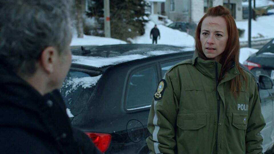 Une femme qui porte une veste de policière a du sang sur le front.