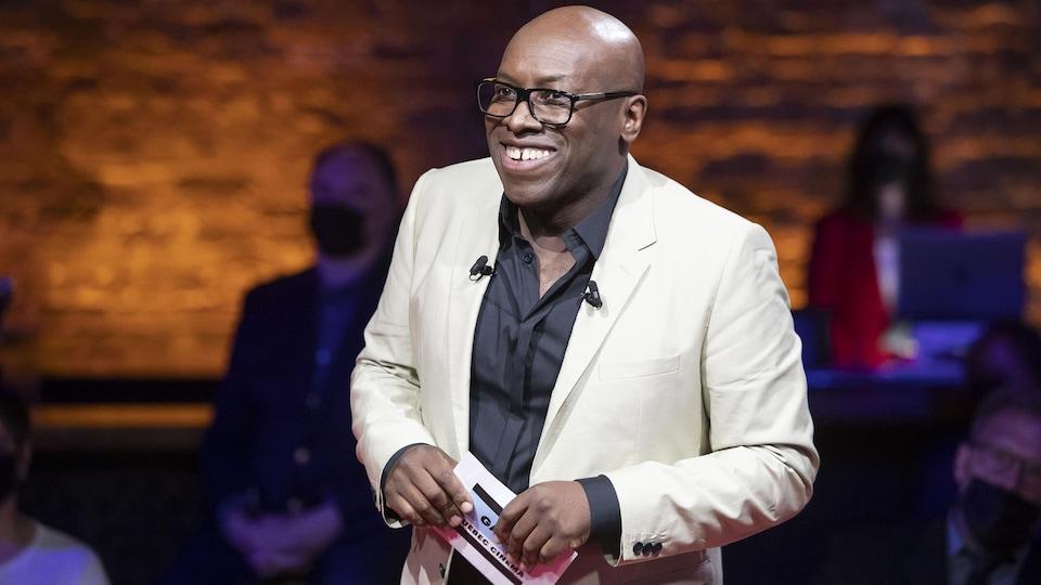 Un homme portant un veston blanc sourit.