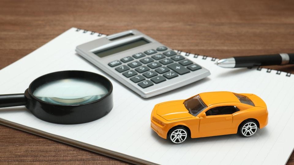 Une loupe, un document et une voiture miniature.
