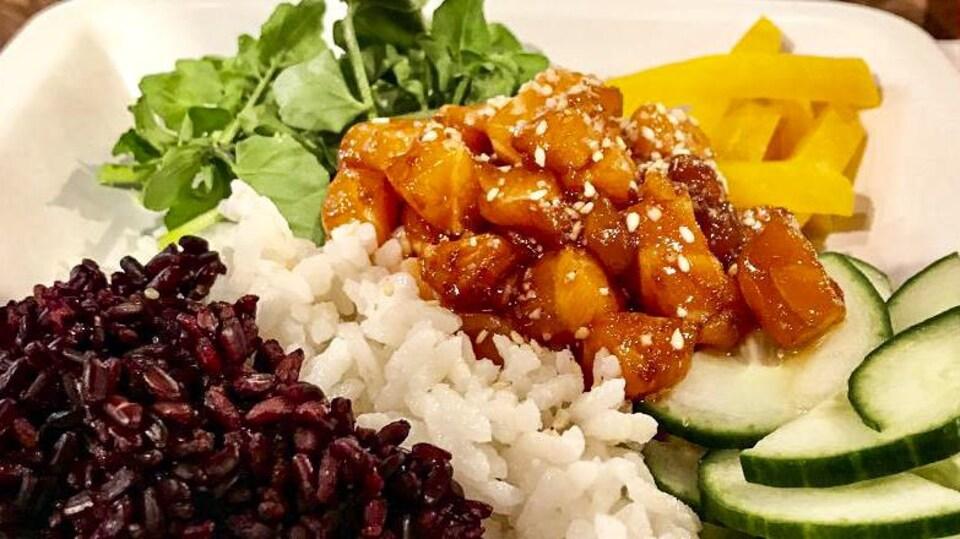 L'assiette est composée de riz, de poisson, de betteraves et de concombre