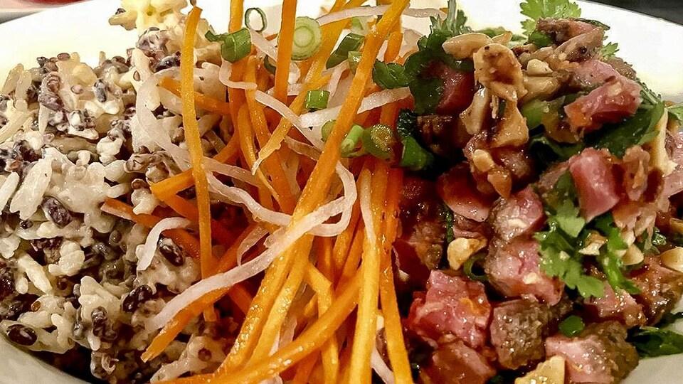 Le bol est composé de riz, de viande, de carottes râpées et d'herbes fraîches