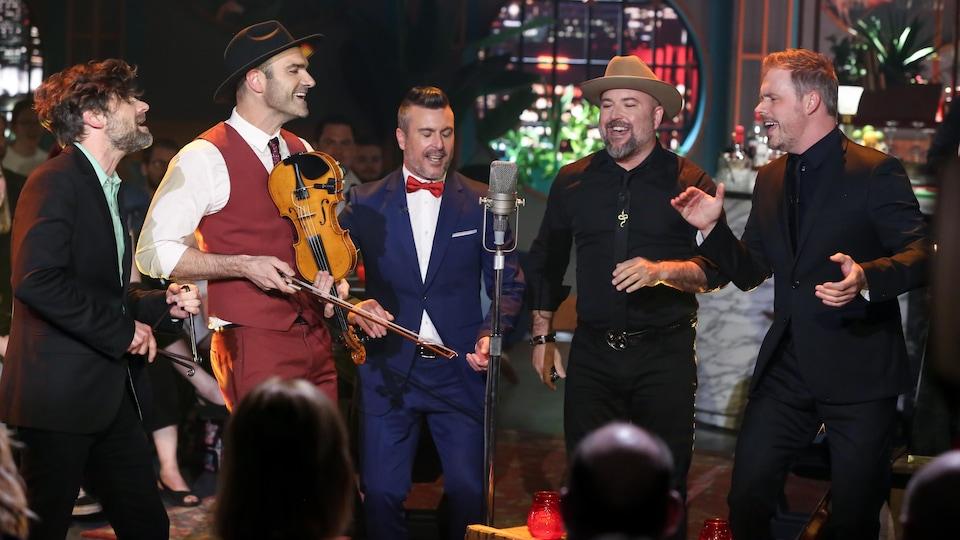 Cinq chanteurs et musiciens autour d'un micro.