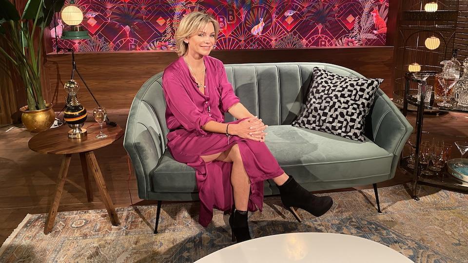 Caroline Néron, qui porte une robe fuchsia, est assise sur un divan.