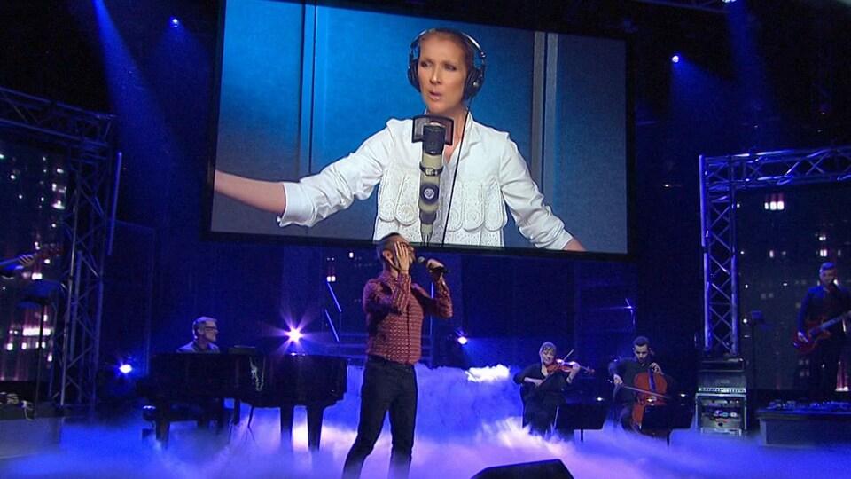 Céline est sur un écran et Pierre est sur scène accompagné par des musiciens.
