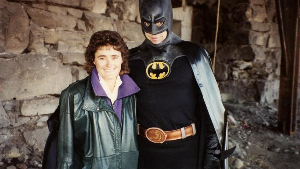 Dans un décor tout en pierre, la réalisatrice de Découverte Jeannita Richard et l'animateur Charles Tisseyre déguisé en Batman sourient.