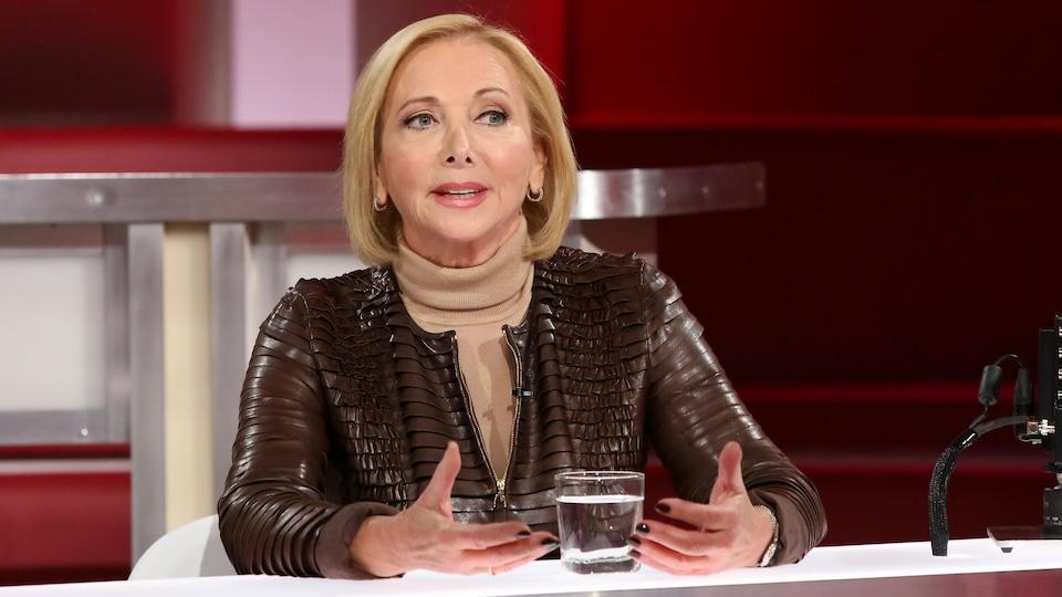 Christiane Germain est à la table des invités. Elle porte un chandail à col roulé beige et une veste en cuir brun.