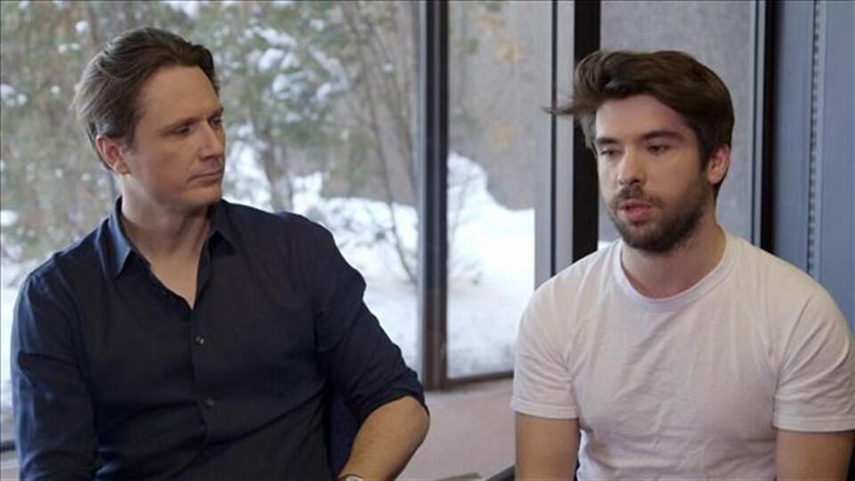 Le réalisateur et le producteur sont en entrevue, assis près d'une fenêtre.