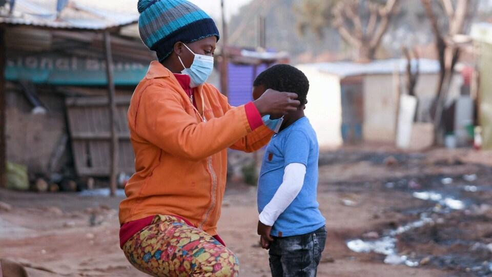 Une mère africaine met un masque à son fils.