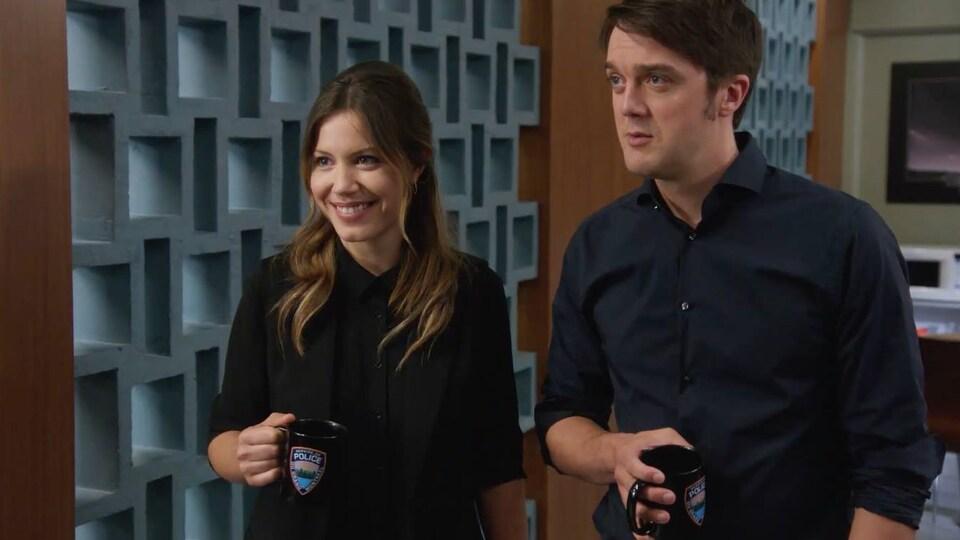 Nadine et Patrick regardent droit devant eux en souriant avec une tasse de café dans les mains.