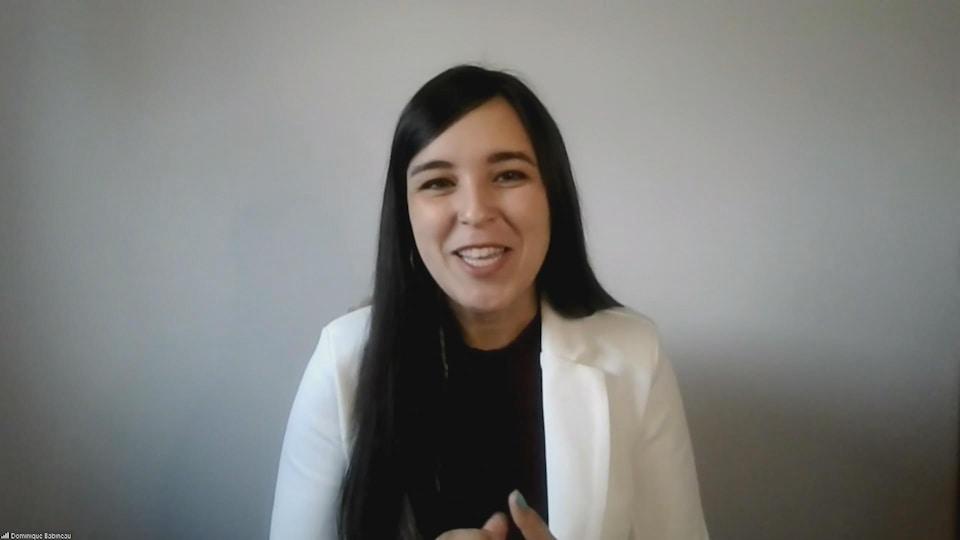 Une femme avec de long cheveux noirs et un veston blanc.
