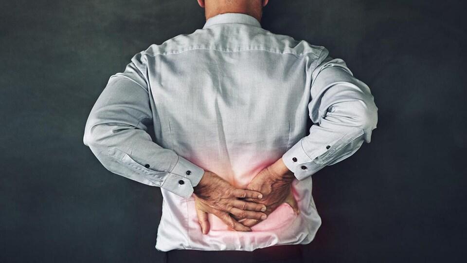 Un homme qui se tient le bas du dos, car il a de la douleur.
