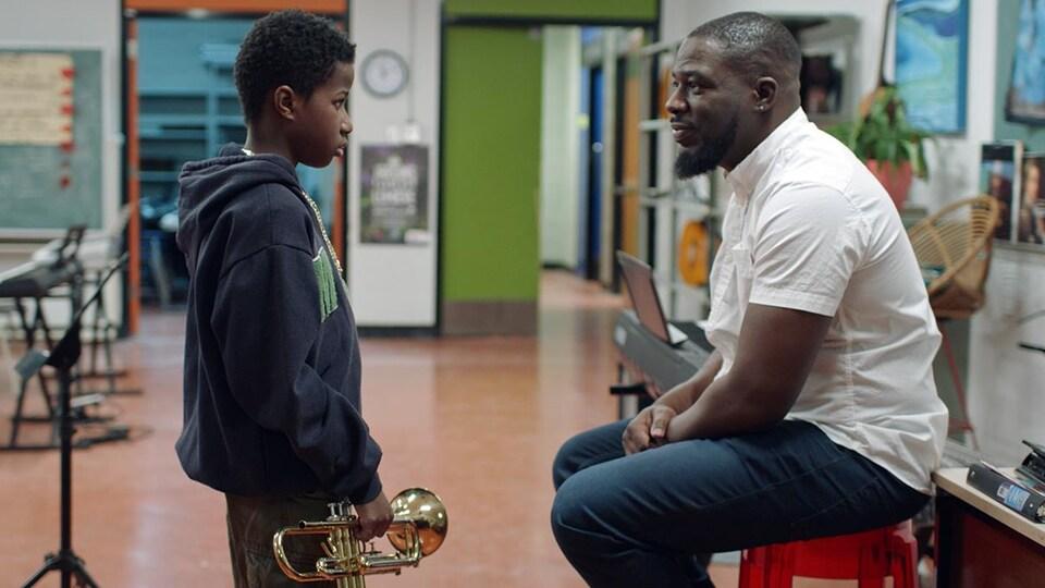 Un enfant, qui tient une trompette, et son professeur se regardent.