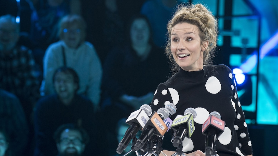 Elle est devant 5 micros dans une simulation de conférence de presse.