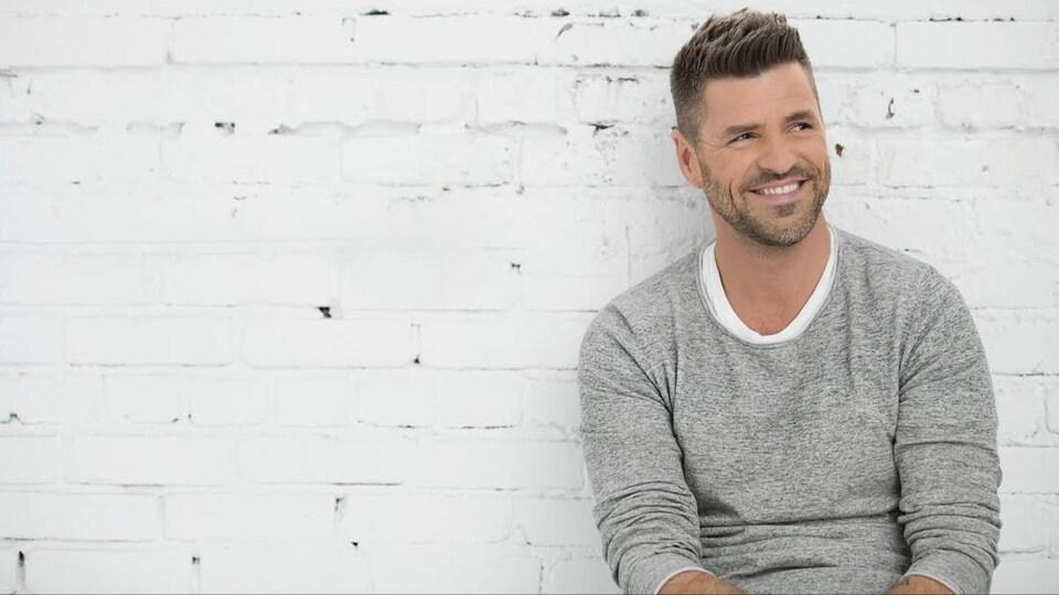 Marc Dupré, souriant, pose devant un mur en briques blanches.